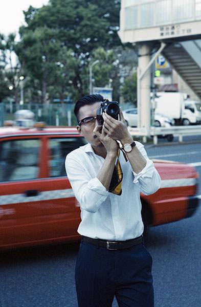 シャツを着てカメラを構える男性